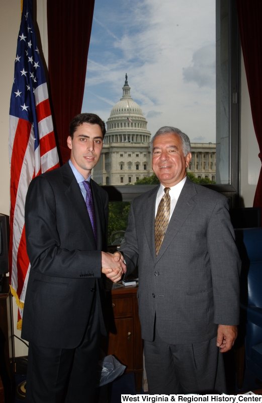 Congressman Rahall stands in his Washington office with a man wearing a black suit and purple tie.