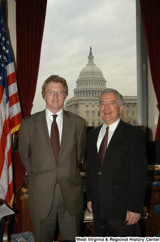 Congressman Rahall stands in his Washington office with a man wearing a brown suit.