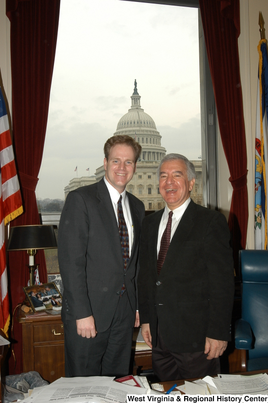 Congressman Rahall stands in his Washington office with a man wearing a dark grey suit.