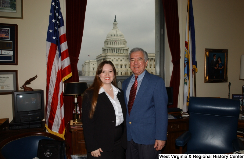 Congressman Rahall stands in his Washington office with a woman wearing a white striped blouse and black jacket.