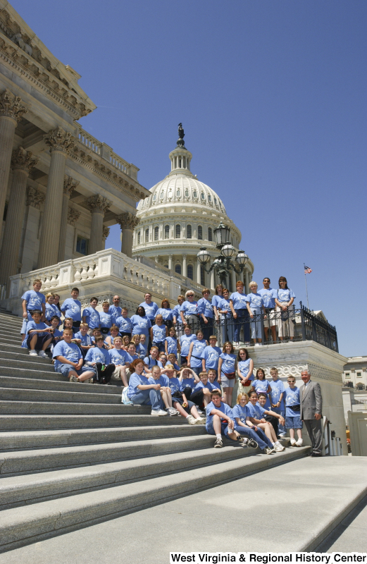 Congressman Rahall stands on the steps of the Capitol Building with children and adults wearing blue shirts containing an image of West Virginia.