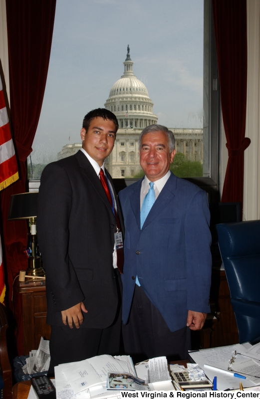 Congressman Rahall stands in his Washington office with a man wearing a dark suit, red tie, and Presidential Classroom badge.