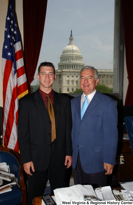 Congressman Rahall stands in his Washington office with a man wearing a dark suit, bronze tie, and burgundy shirt.