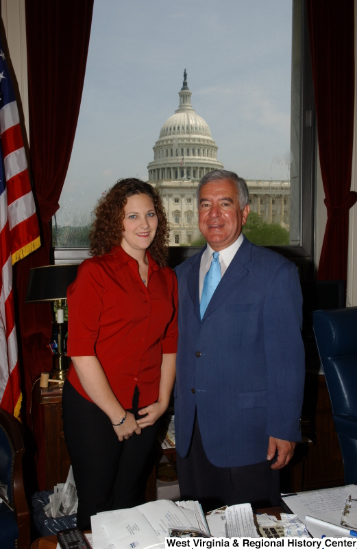 Congressman Rahall stands in his Washington office with a woman wearing a red shirt.