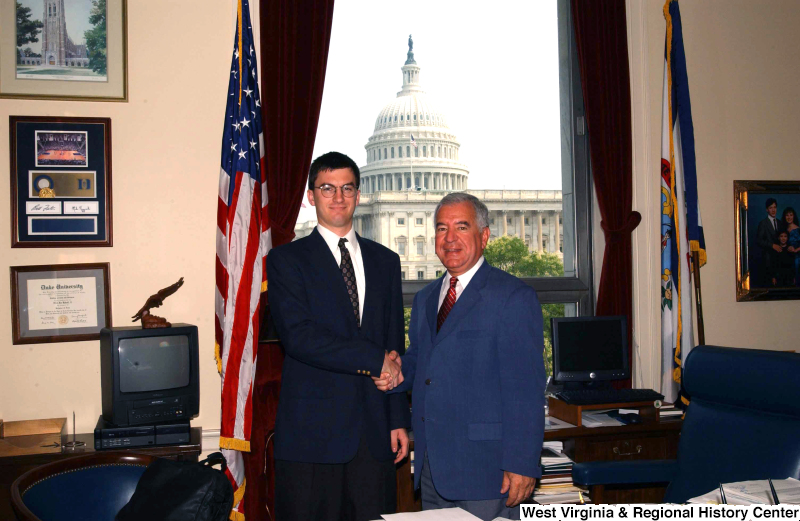 Congressman Rahall in his Washington office shakes hands with a man in a dark blue suit.