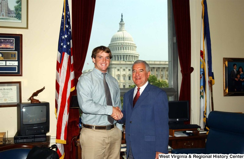Congressman Rahall stands in his Washington office with a man wearing a blue-tinged shirt and khaki pants.
