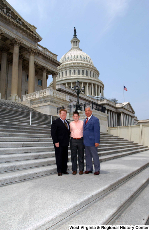 Congressman Rahall stands on the steps of the Capitol Building with a man and boy.