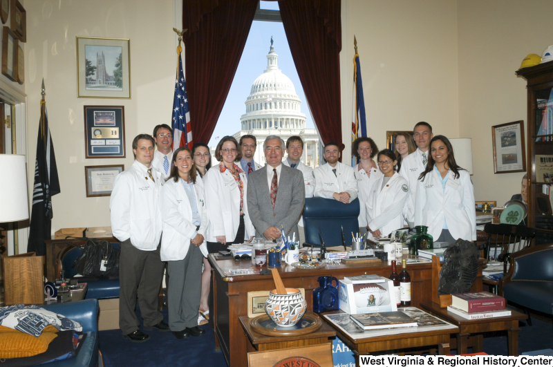 "Congressman Rahall stands in his Washington office with a group of people wearing lab coats with ""WVSOM"" on front."