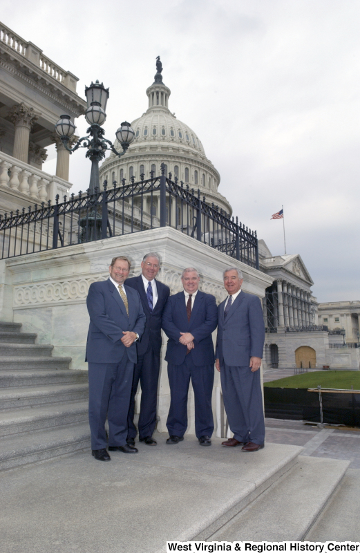 Congressman Rahall stands on the steps of the Capitol Building with three men wearing suits.