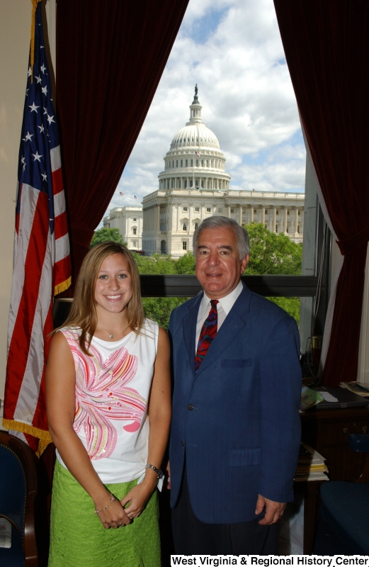 Congressman Rahall stands in his Washington office with a woman wearing a floral-print shirt and green skirt.