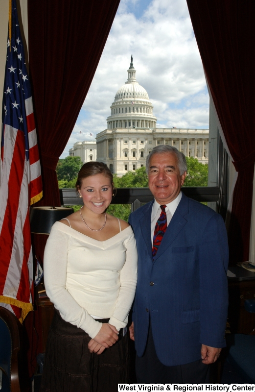 Congressman Rahall stands in his Washington office with a woman wearing a white top and brown skirt.