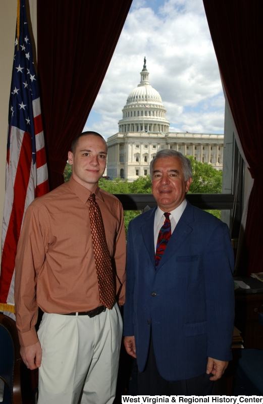 Congressman Rahall stands in his Washington office with a man wearing an orange-tinted shirt and red tie.