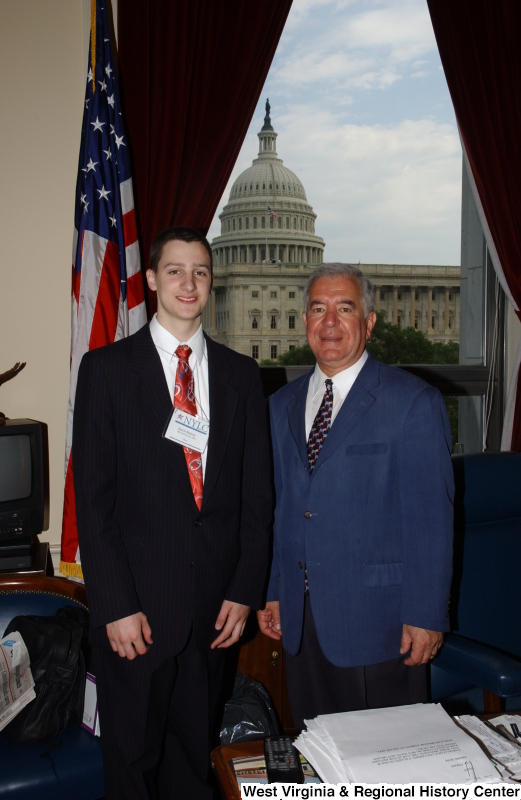 Congressman Rahall stands in his Washington office with a young man wearing a NYLC badge.