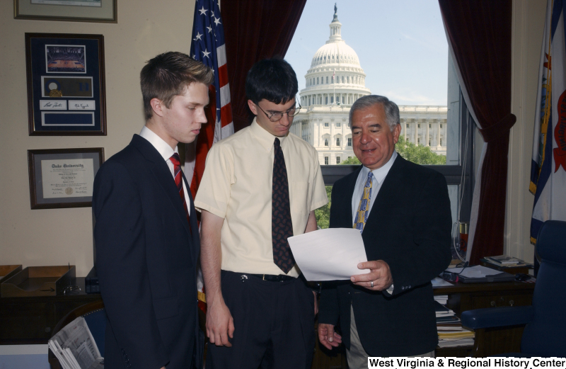 Congressman Rahall in his Washington office looks at a paper with two young men.