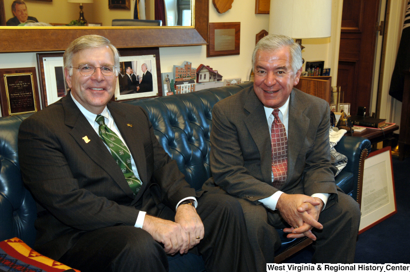 Congressman Rahall sits with a man wearing a green Marshall University tie and pin.