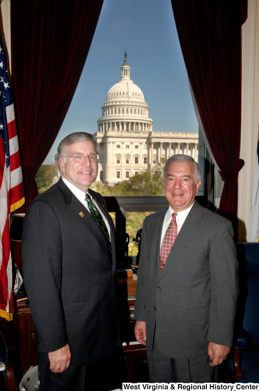 Congressman Rahall stands in his Washington office with a man wearing a green Marshall University tie and pin.