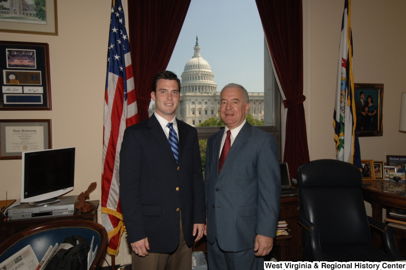 Congressman Rahall stands in his Washington office with a man wearing a dark blazer and blue striped tie.