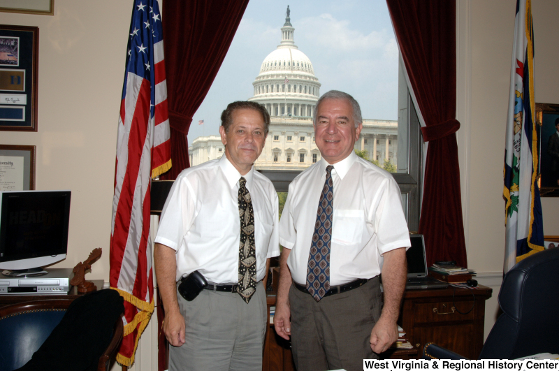 Congressman Rahall stands in his Washington office with another man wearing white short-sleeve shirts.