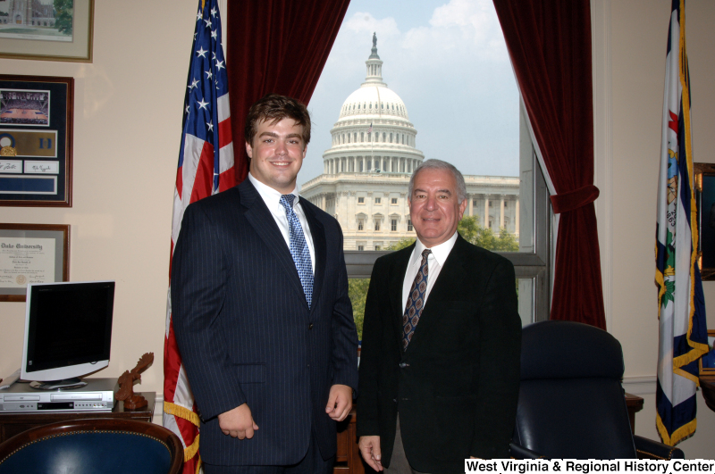 Photograph of Congressman Rahall in his Washington office standing with a man wearing a dark pinstripe suit and blue tie