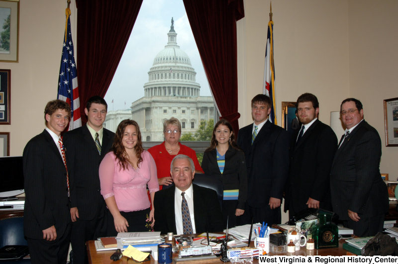 Congressman Rahall sits in his Washington office with a group of five men and three women.