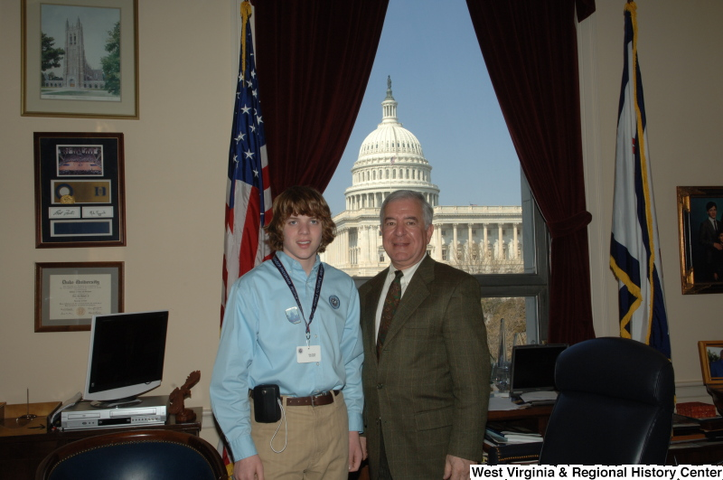 Congressman Rahall stands in his Washington office with a young man wearing a People To People Ambassador Programs lanyard.