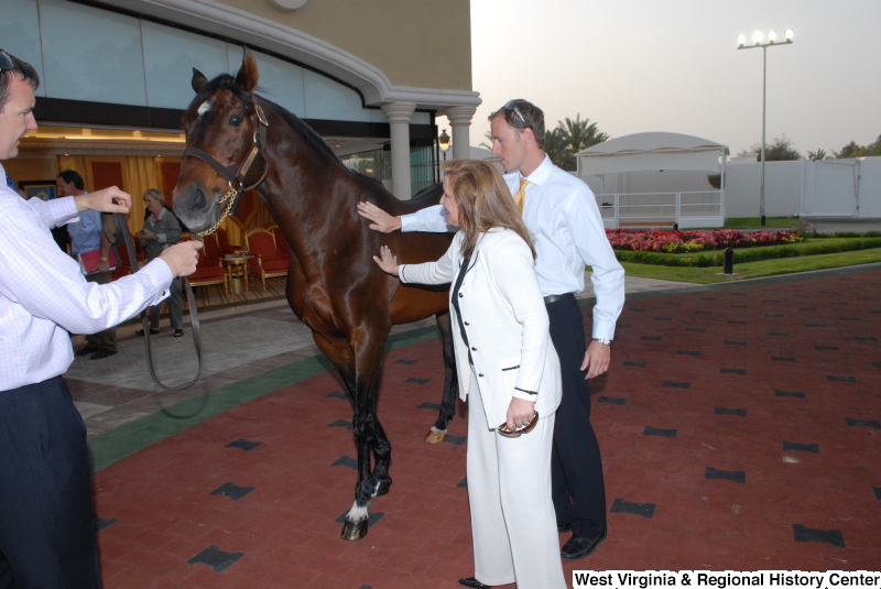 People stand with a horse during a Congressional Delegation trip to Saudi Arabia.