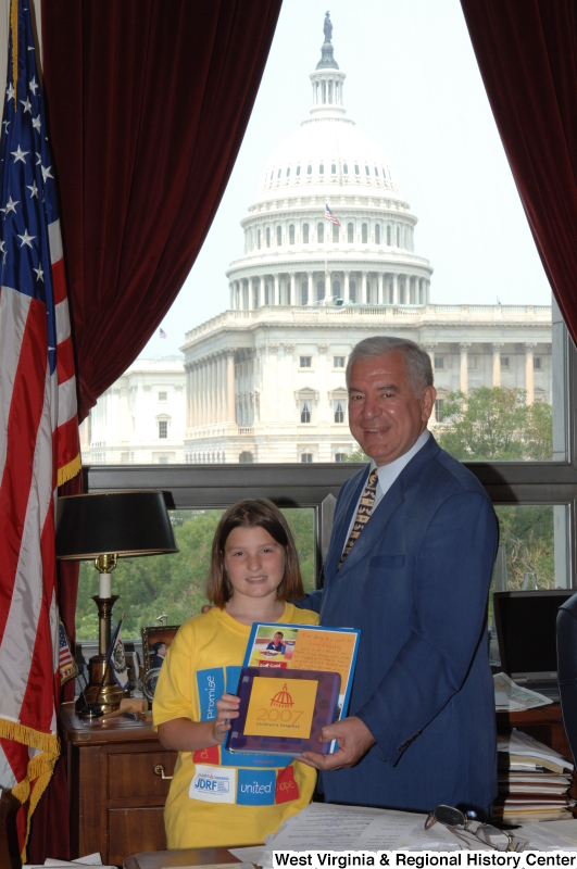 Congressman Rahall stands in his Washington office with a girl holding materials labeled 2007 Children's Congress and wearing a shirt with the logo for Juvenile Diabetes Research Foundation International.