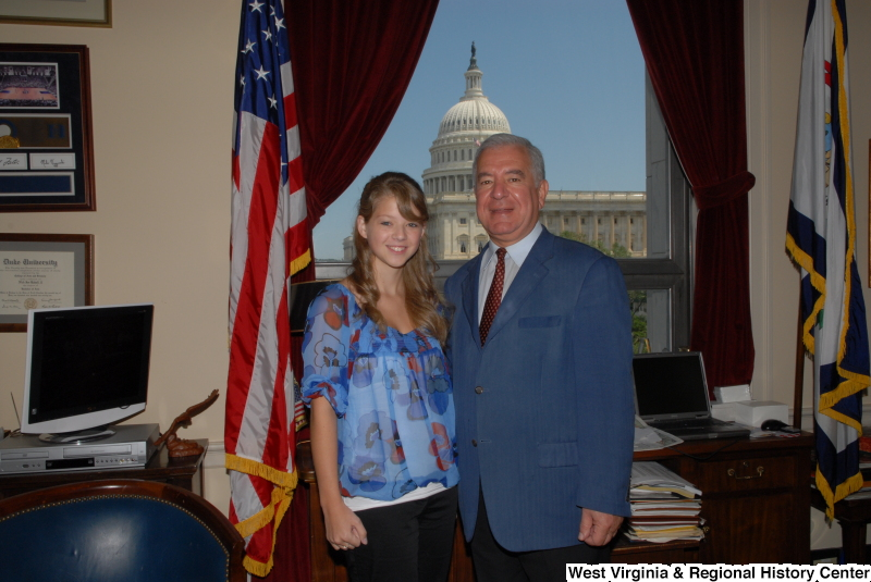Congressman Rahall stands in his Washington office with a woman wearing a blue and red blouse.