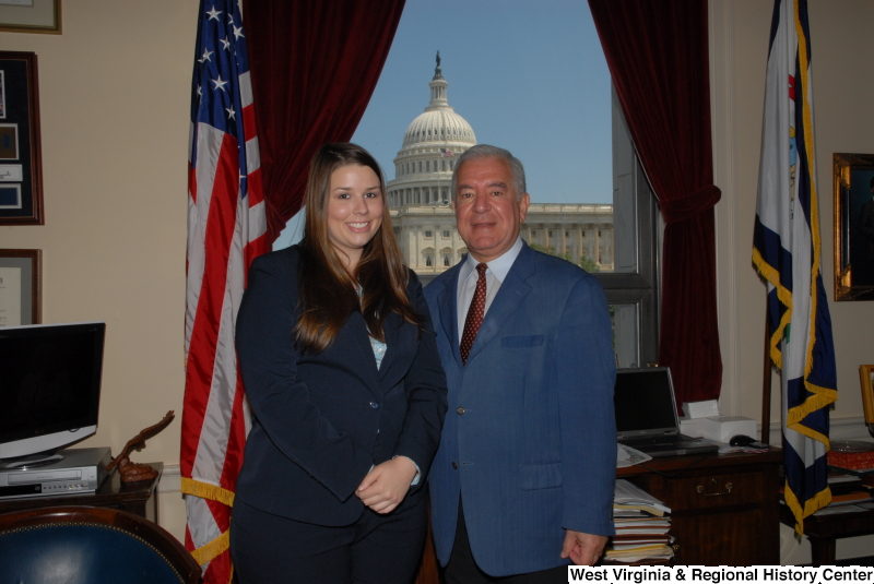 Congressman Rahall stands in his Washington office with a woman wearing a dark blue top and pants.
