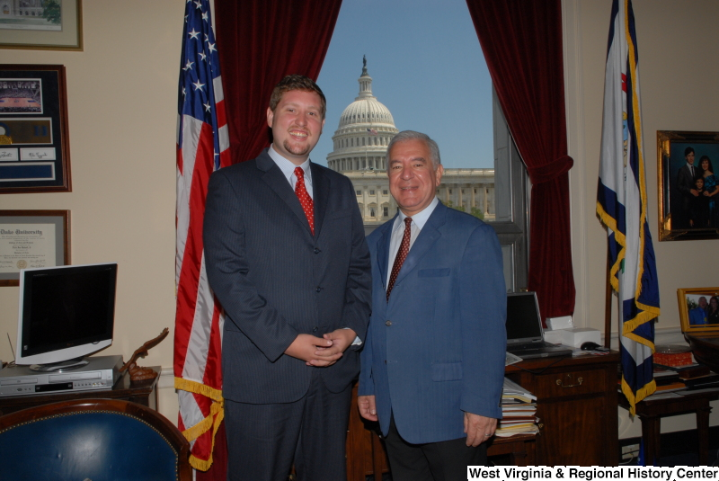 Congressman Rahall stands in his Washington office with a man wearing a dark blue pinstripe suit and red tie.