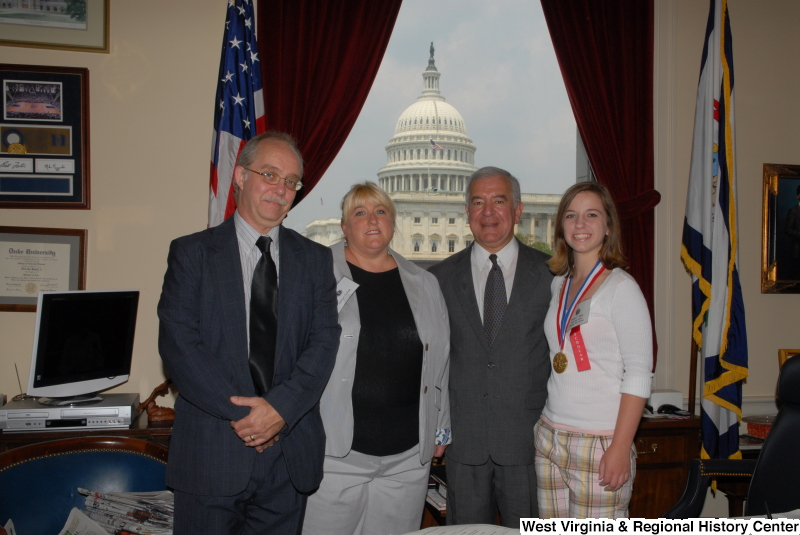 "Congressman Rahall stands in his Washington office with Scott High School student Sarah Dolan, who wears a medal and ""scholar"" ribbon, Sonya Dolan, and another man."