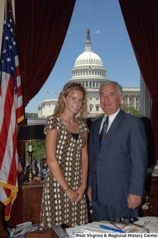 Congressman Rahall stands in his Washington office with a woman wearing a brown, white, and black dress.