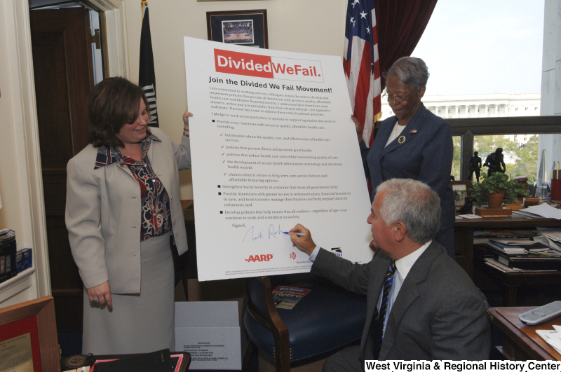Congressman Rahall signs a poster-sized pledge for the Divided We Fail Movement, with two women.