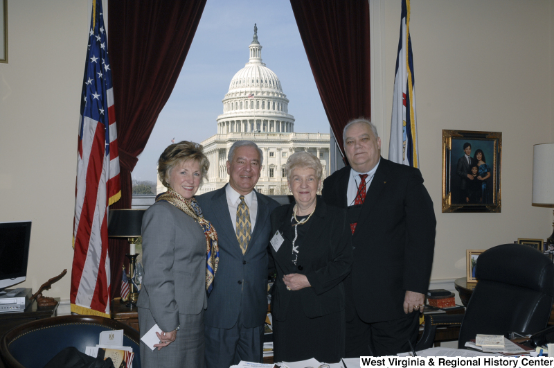 Congressman Rahall stands in his Washington office with a man and two women.