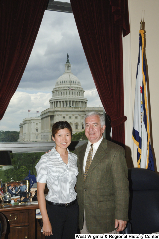 Congressman Rahall stands in his Washington office with a woman wearing a striped short-sleeve shirt.
