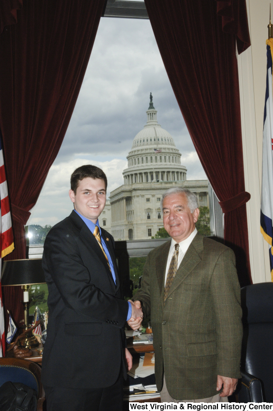 Congressman Rahall in his Washington office shakes hands with a man wearing a dark suit and light blue shirt.