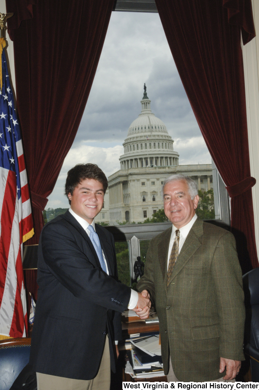 Congressman Rahall in his Washington office shakes hands with a man wearing a dark blazer and light blue tie.