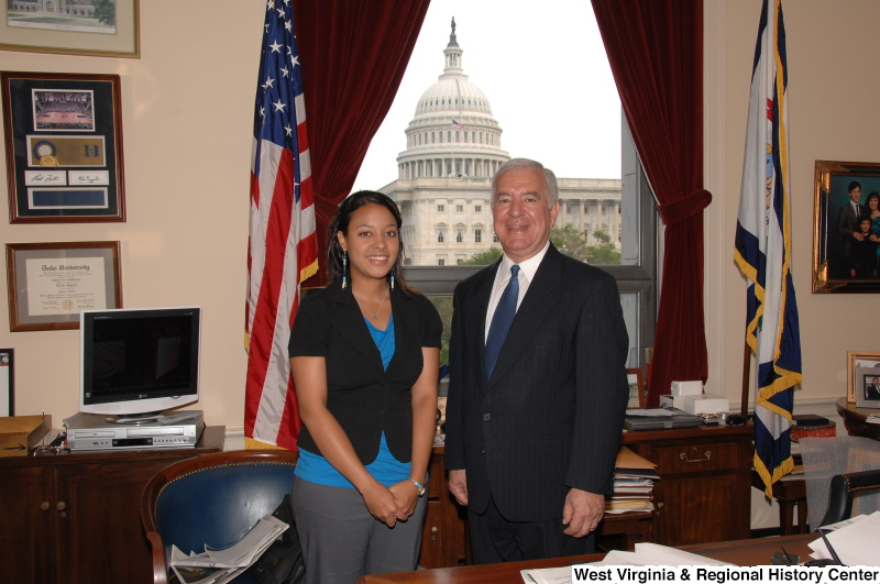 Congressman Rahall stands in his Washington office with a woman wearing a blue shirt and black short-sleeved jacket.