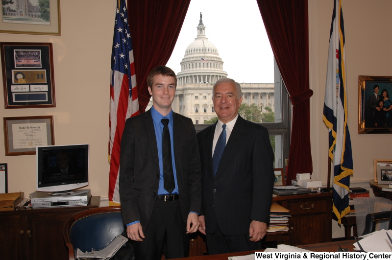 Congressman Rahall stands in his Washington office with a man wearing a black suit, blue shirt, and black tie.