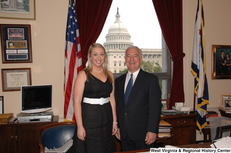 Congressman Rahall stands in his Washington office with a woman wearing a dark dress with white belt.