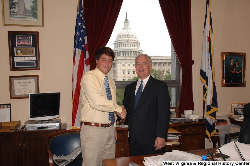 Congressman Rahall in his Washington office shakes hands with a man wearing an orange-tinged shirt.