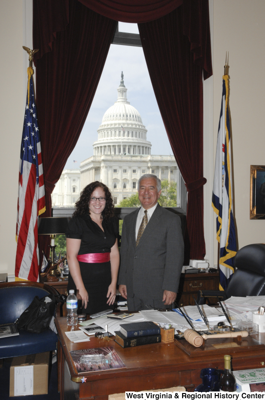 Congressman Rahall stands in his Washington office with a woman wearing black clothing and a red sash.