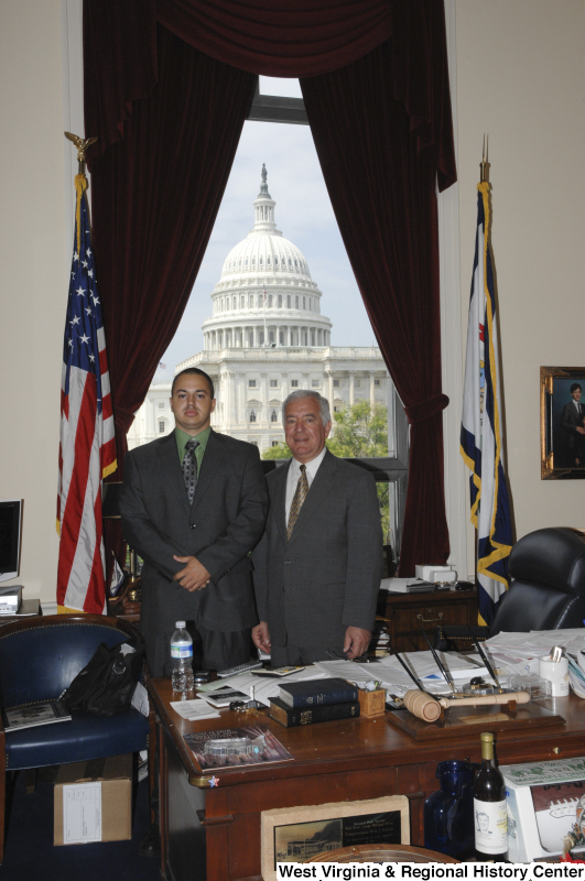 Photograph of Congressman Rahall standing in his Washington office with a man wearing a grey suit and green shirt