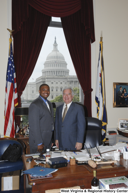 Congressman Rahall stands in his Washington office with a man wearing a grey suit, blue shirt, and light tie.