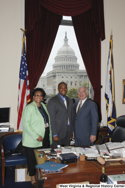 Congressman Rahall stands in his Washington office with a man wearing a grey suit, blue shirt, and light tie, and a woman wearing a light green sport coat.