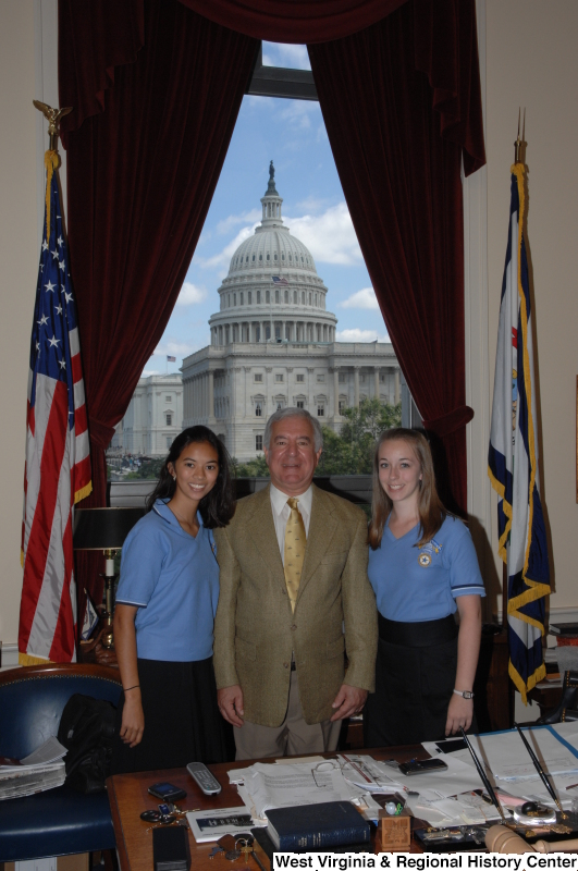 Congressman Rahall stands in his Washington office with two young women wearing blue shirts.