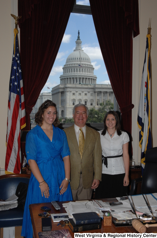Congressman Rahall stands in his Washington office with a woman wearing a blue dress and a woman wearing a white and black-dotted shirt.