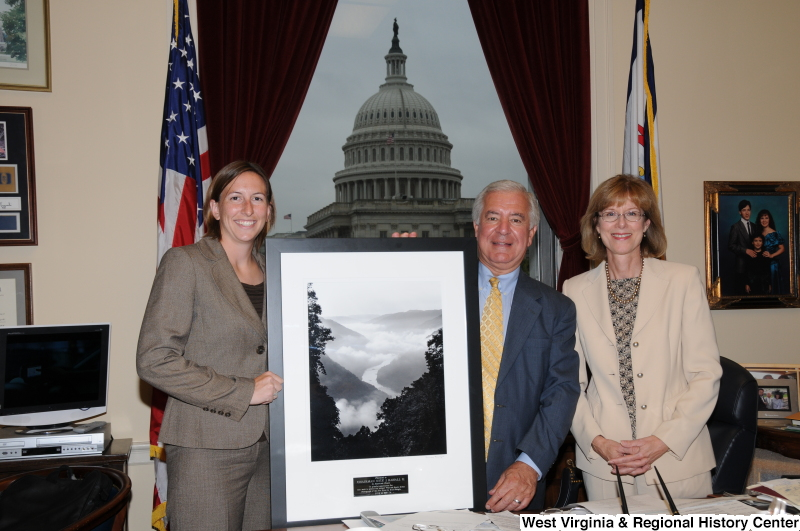 Congressman Rahall stands in his Washington office with two women next to a framed photograph of the New River presented by American Rivers.