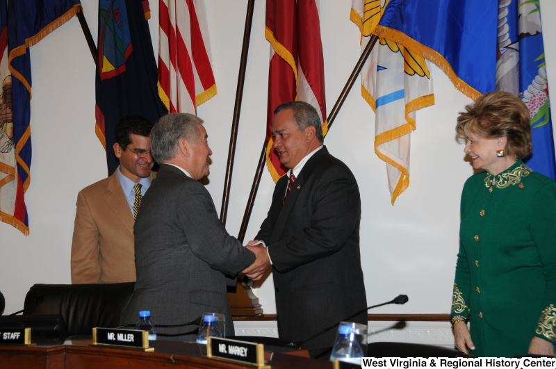 Congressman Rahall shakes hands with Gregorio Sablan in front of flags, while others look on.
