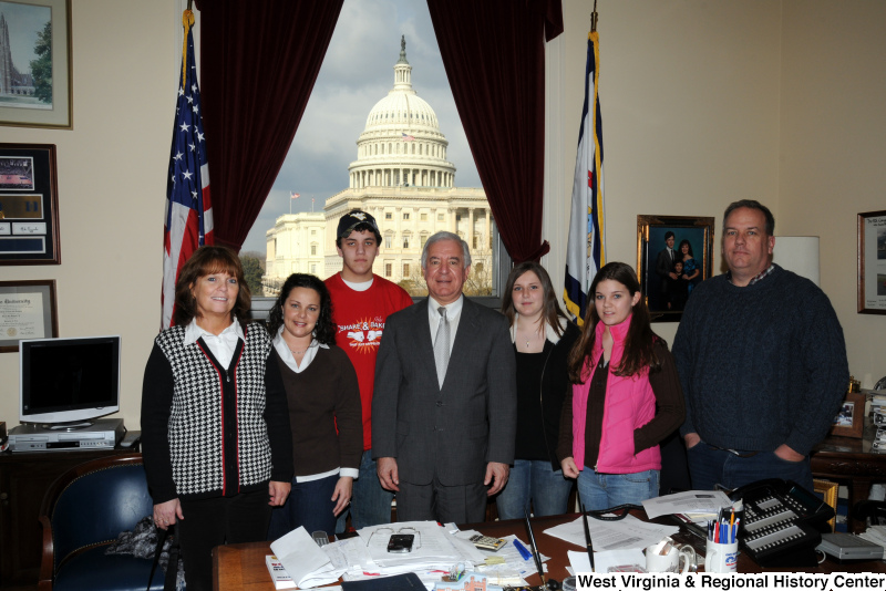 Congressman Rahall stands in his Washington office with adults and teenagers.